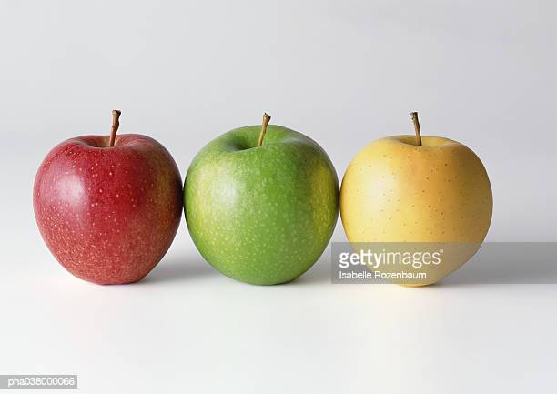 Three apples in a row, red, green, yellow, close-up