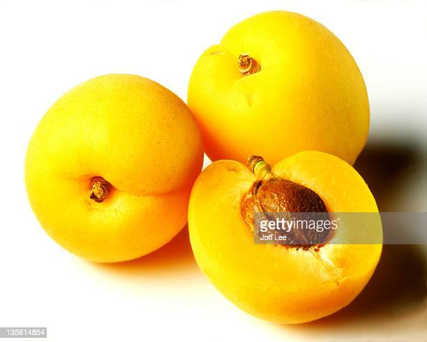Three apricots one halved showing stone