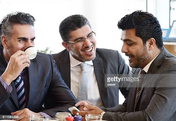 Three arab business men in cafe