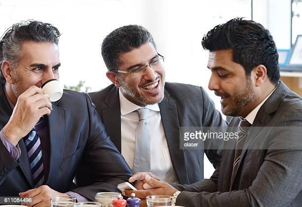 Trois hommes d'affaires dans un café arabe