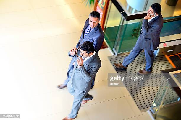 Three arab business men in suits walking into bright light