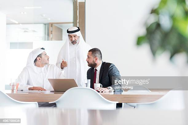 three arab businessmen in business meeting in modern office - gulf countries stock pictures, royalty-free photos & images