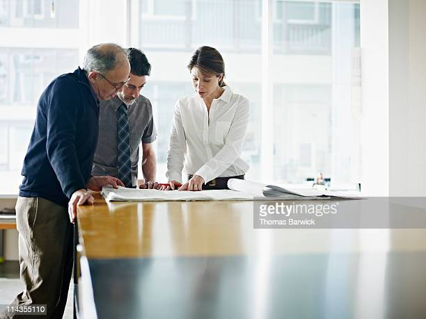 Three architects examining plans at desk in office