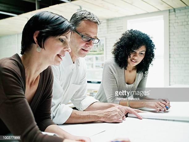 Three architects examining plans on desk
