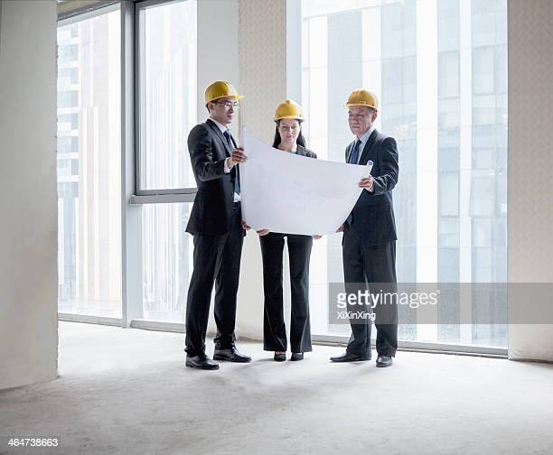 Three architects in hardhats examining a blueprint in an office building