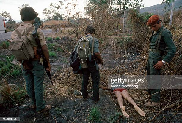 Three armed guerrillas from Fuerzas Populares de Liberacion stand beside a dead body from the government security forces along a highway near...