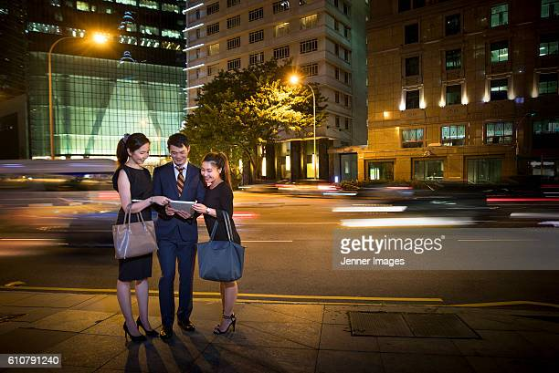 Three Asian business collegues looking at a Tablet device at night with traffic light trails in background.