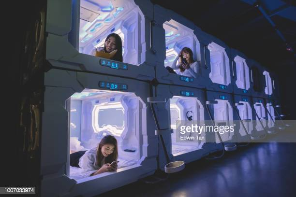 three asian chinese female tourist check in capsule hotel room and surfing internet and selfie on their bed with their mobile phone while one of them reading from her notebook