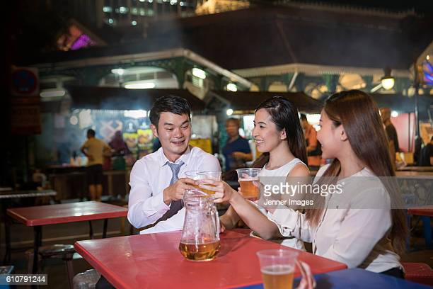 Three Asian friends having dinner and drinks at street food market after work.
