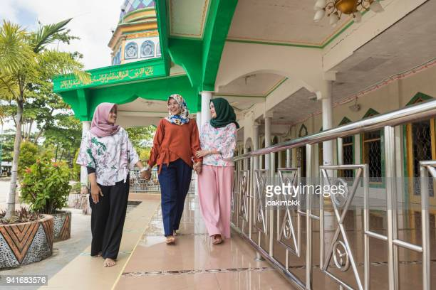three asian muslim young women walking cheerfully at the mosque - place of worship stock pictures, royalty-free photos & images