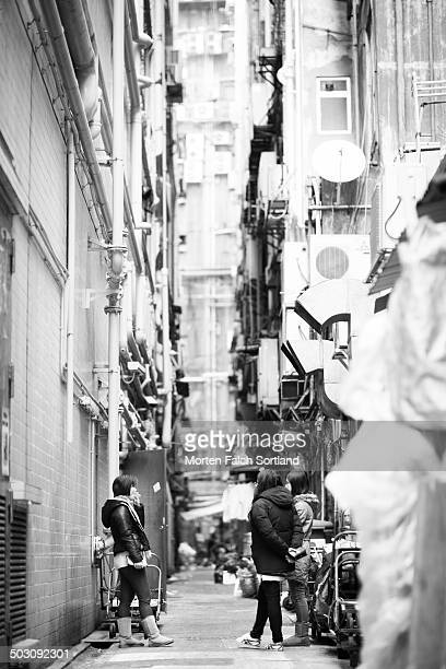 Three Asian woman smoking cigarettes in a back alley in Hong Kong