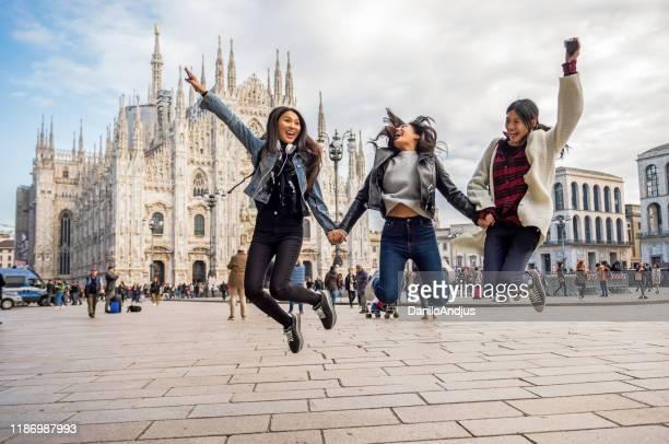 tre donne asiatiche saltano intorno alla piazza della città - piazza del duomo milano foto e immagini stock