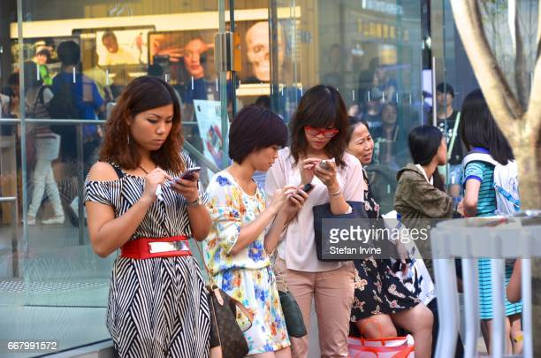 Three Asian women using iPhone smartphones outside the Apple Store in Hong Kong