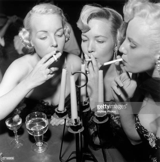 Three aspiring actors Shirley Buchanan Mara Lynn and Donna Williams light their cigarettes from a candelabra at a bar Loreto Mexico