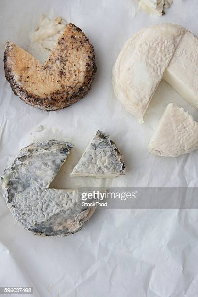 three assorted goat cheese wheels; each with a wedge removed; from above - crosta di formaggio foto e immagini stock