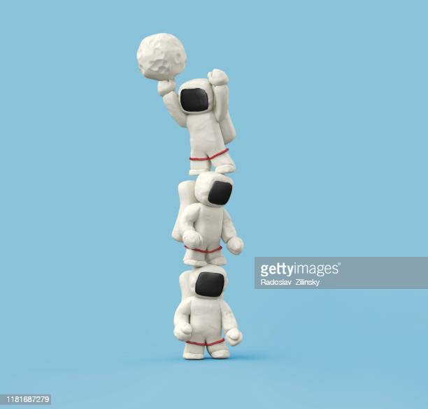three astronauts playing with ball on top of each other - clay stock pictures, royalty-free photos & images