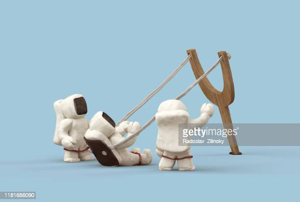 three astronauts shooting out of slingshot - animation stock pictures, royalty-free photos & images