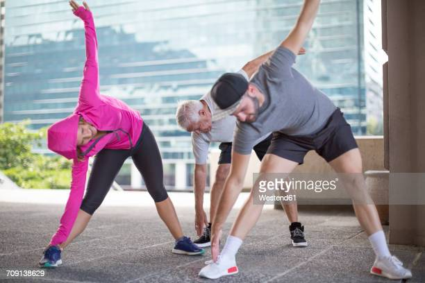 Three athletes doing gymnastics in the city