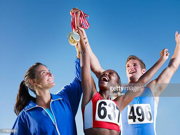 three athletes holding medals up over their heads - medalist stock pictures, royalty-free photos & images