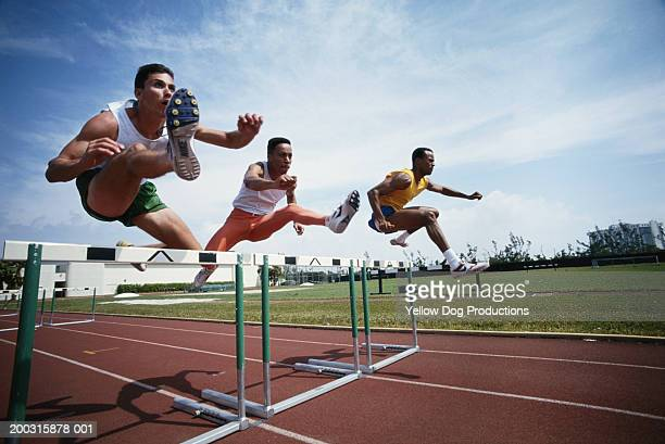 three athletes jumping hurdle - hurdling track event stock pictures, royalty-free photos & images