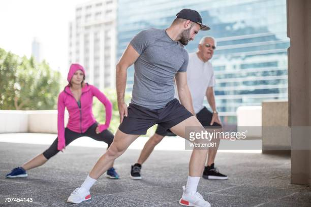 Three athletes stretching in the city