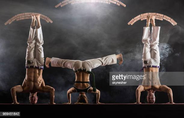 three athletic people exercising headstand on capoeira training in a health club. - traditional dancing stock photos and pictures