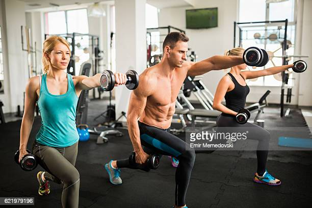 Three attractive people doing lunges with dumbbells. Side view.
