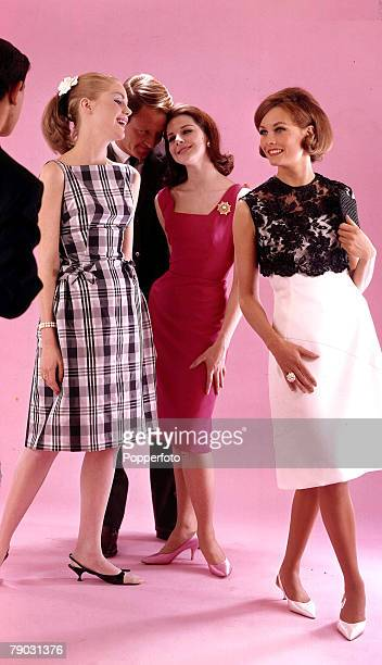 1963 Three attractive young women wearing fashionable eveningwear socialise with two smartly dressed men The women are wearing lr a sleeveless black...