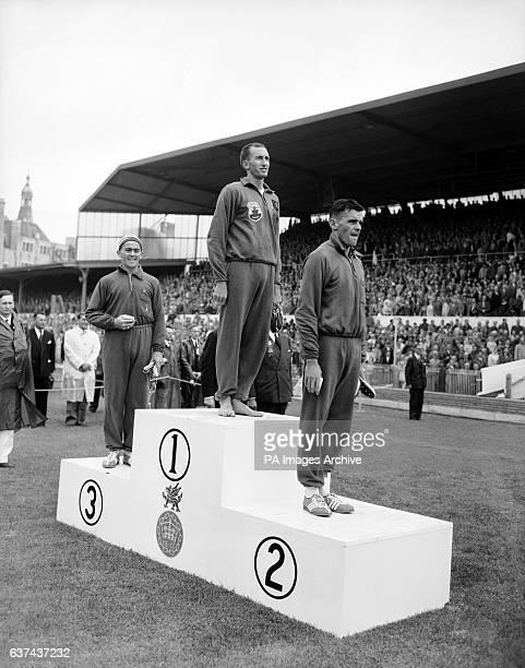 Three Australians stand on the podium to receive their medals for the men's mile bronze medallist Albert Thomas gold medallist Herb Elliot silver...