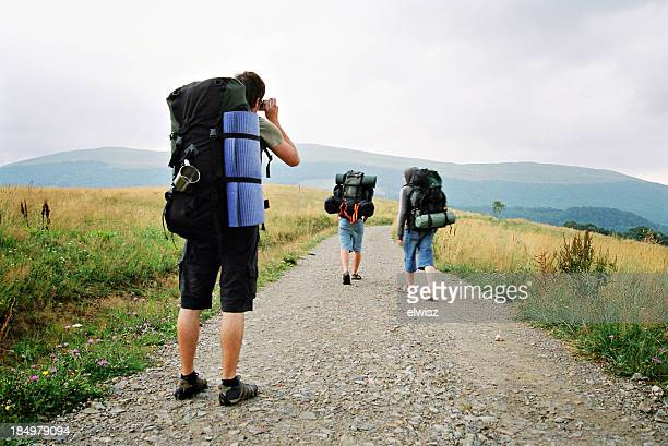 Three backpackers on a road with one of them taking pictures