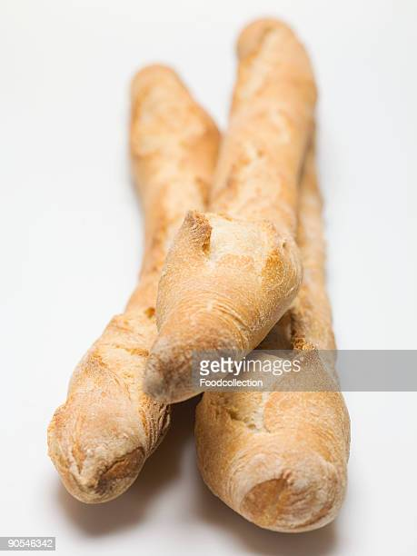 Three baguettes on white background, close up