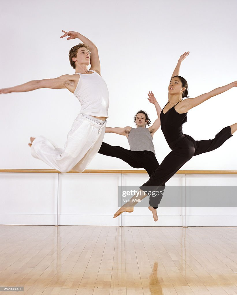Three Ballet Dancers Jumping in Mid Air With One Arm Raised : Stock Photo
