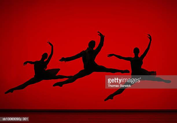 three ballet dancers leaping on stage, silhouette - uitvoerende kunst voorstelling stockfoto's en -beelden