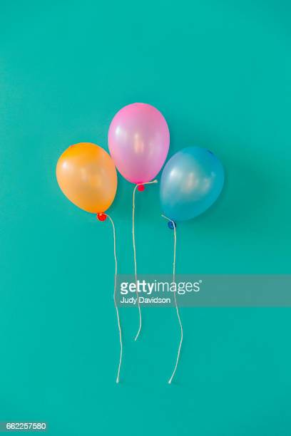 three balloons on an plain aqua background - three objects stock pictures, royalty-free photos & images