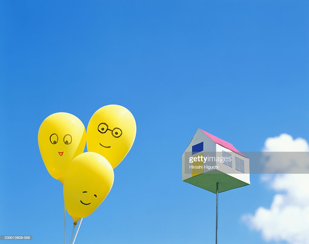 three balloons with faces drawn on them beside toy house on stick