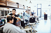 three barbers working clients hair barber
