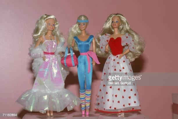 Three barbie dolls on display 1980s One doll is dressed in a shiny ball gown and stole another in a heartdecorated gown and the third dressed in...