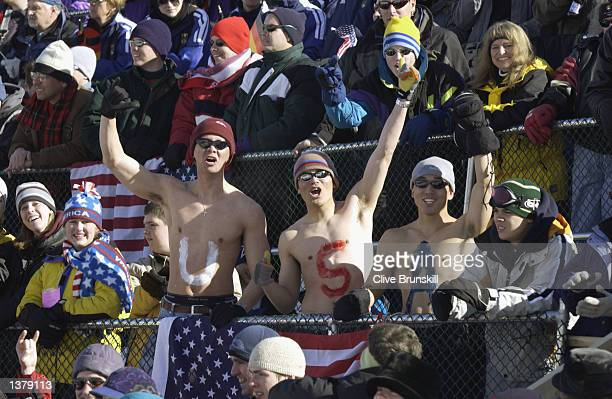 Three bare chested male fans spell out USA with paint on their bodies as they cheer in the final round of the women's halfpipe snowboarding event...