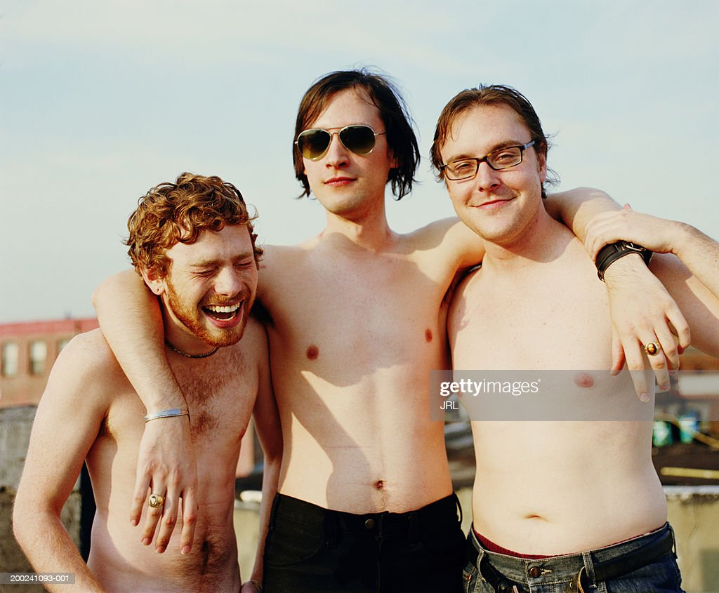 Three barechested young men embracing on rooftop, portrait : Stock Photo