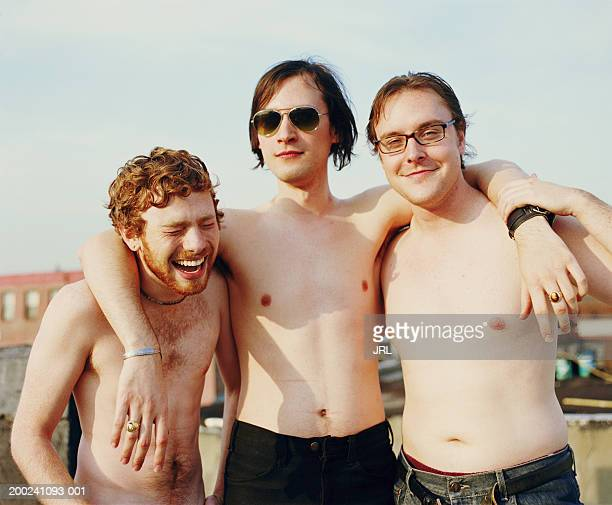 Three barechested young men embracing on rooftop, portrait