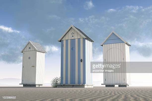 Three beach huts on an empty beach