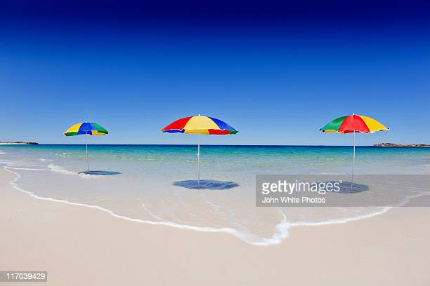 Three beach umbrellas on pristine beach