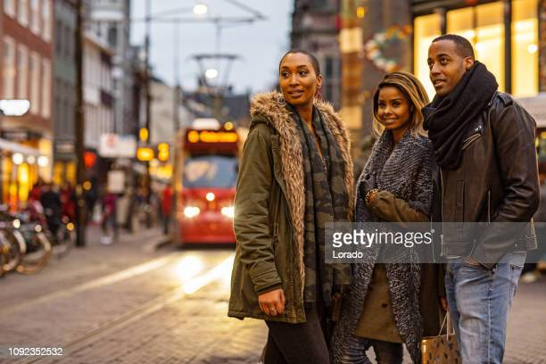 three beautiful black friends at christmas shopping - hague market stock pictures, royalty-free photos & images