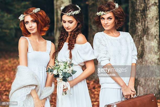 Three beautiful bride on a background of autumn forest