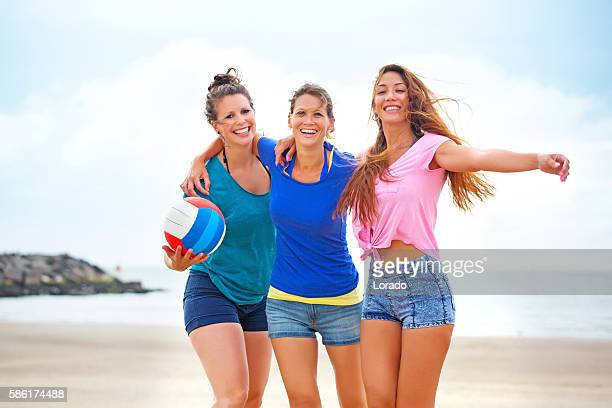 Three beautiful casual female friends celebrating on a beach