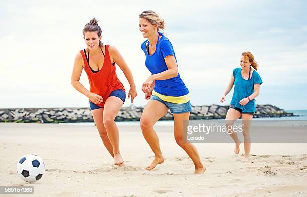 three beautiful female friends playing beach soccer in summer - ビーチサッカー ストックフォトと画像