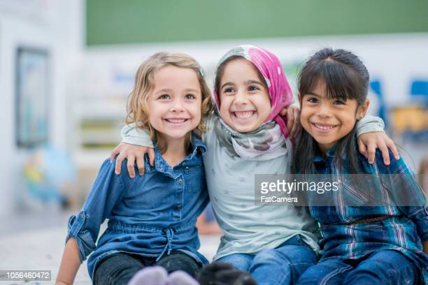 three beautiful girls smile facing forward - first day of school stock pictures, royalty-free photos & images
