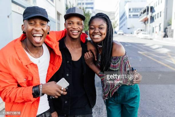 three beautiful happy embracing friends laughinginto camera on city street - república da áfrica do sul imagens e fotografias de stock