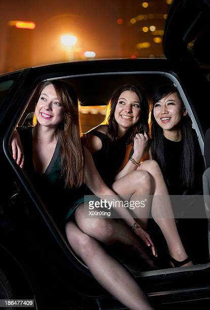Three beautiful women arriving at a red carpet event in a car, night, Beijing