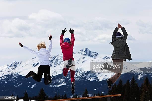 Three beautiful women having fun jump off a picnic table in Colorado.
